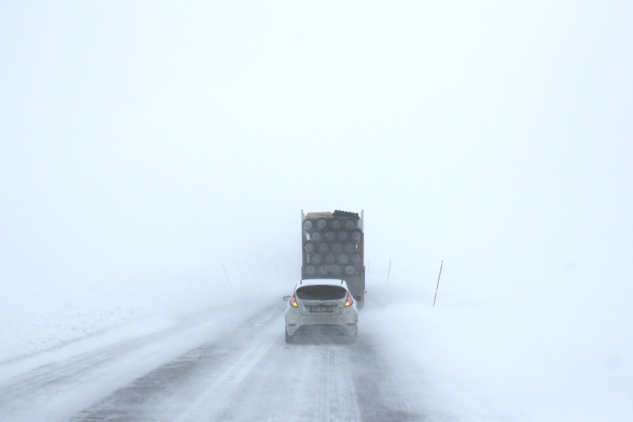 Car following lorry in the snow